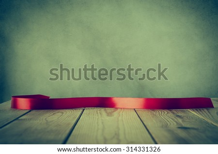 A red satin ribbon, curved and facing front to provide copy space for message, placed on a wood plank table against parchment background.  Cross processed with vignette for retro or vintage style. - stock photo
