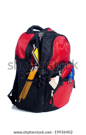 A red school back pack or book bag overflowing with school supplies including, notebooks, pens, pencils, rulers and glue - stock photo