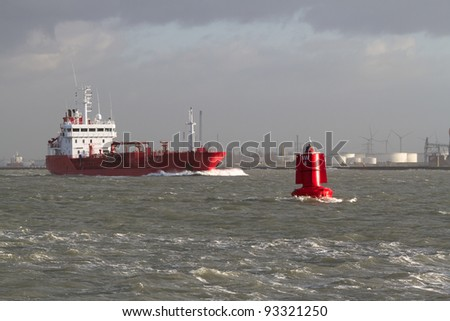 A red ship leaves port - stock photo