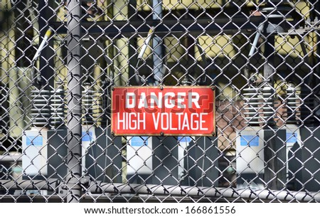A red sign reading DANGER HIGH VOLTAGE at an electrical substation - stock photo