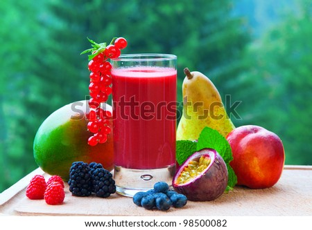 A red smoothie with a collection of tropical fruit.