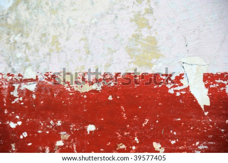 A red stripe of paint on an old stucco wall imitates modern art