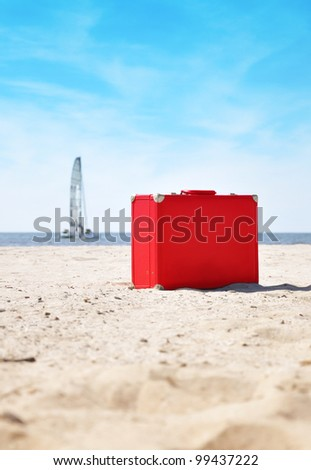 A red suitcase is on the beach with a sailboat in the background on water. There is sand and it is a sunny day. Use it for a vacation or travel concept. - stock photo