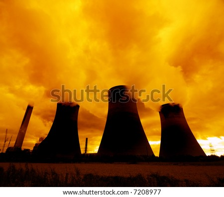 A red sunset looms over a nuclear power plant... - stock photo