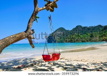 A red swing hanging under a tropical tree on sunny day at Koh Mook island beach, Andaman sea ,Trang, Thailand