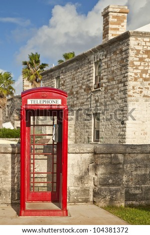 A red telephone box, typical of English influence, in the Royal Naval Dockyard, Bermuda. - stock photo