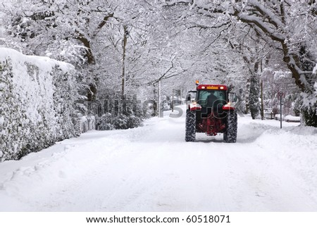 A red tractor driving down a snow covered UK road during the winter snowfall winter in January 2010 - stock photo
