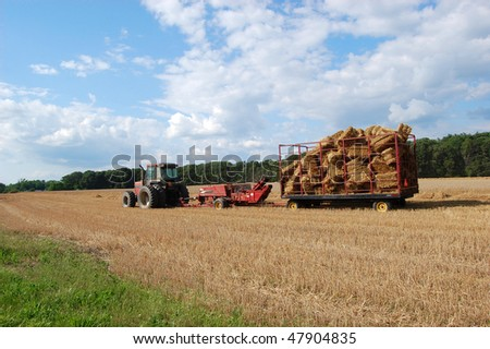 A red tractor pulling a wagon filled with bales of hay - stock photo