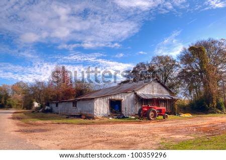 A red tractor stands sentinel outside an old cotton gin storage shed in rural Georgia. - stock photo