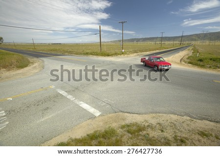 A red truck at a four way intersection of four roads located in the desert near Lancaster, CA - stock photo