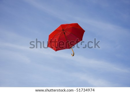 A red umbrella flying on a blue sky - stock photo
