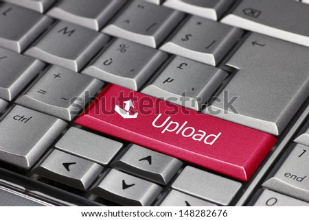 A red upload key on a silver laptop keyboard - stock photo