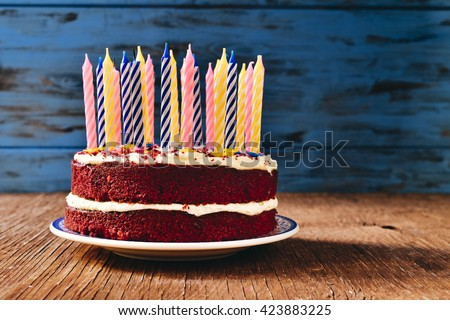 A Red Velvet Cake Topped With Some Unlit Candles On Rustic Wooden Table