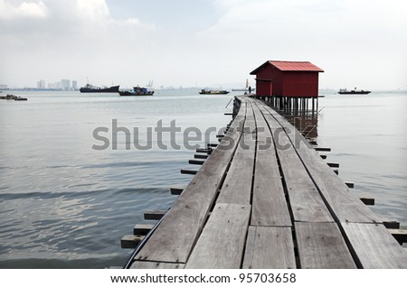 A red vintage Taoist shrine at the end of a timber jetty on the Tan Jetty, which is a UNESCO heritage site, in Penang, Malaysia. - stock photo