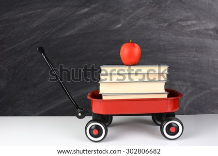 A red wagon full of school books with an apple on top. horizontal format in front of an out of focus chalkboard. Back to School concept with copy space. - stock photo