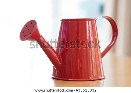 A red watering can isolated on white background