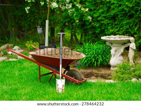 A red Wheelbarrow sits full of dirt in a lush, green garden as spring gardening work is underway.