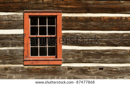 A red window on the wall of a old log cabin. - stock photo