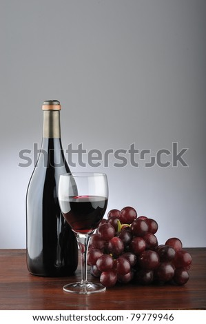 A red wineglass with grapes, bottle and cork - stock photo
