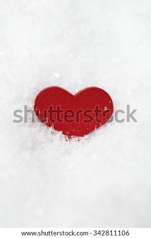 A red wooden heart, partly submerged in white artificial snow, vertically centred with copy space above and below.