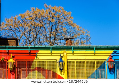 A red, yellow, and blue painted building with three lights and a beautiful blue sky in La Boca neighborhood of Buenos Aires - stock photo