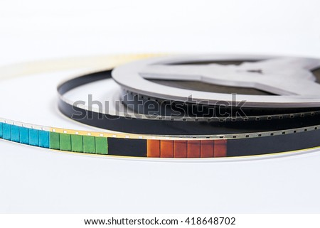 A reel of motion picture film on a white background. Old film strip isolated on white background.