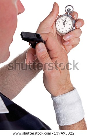 A referee checking his stopwatch and about to blow the whistle, isolated on a white background. - stock photo