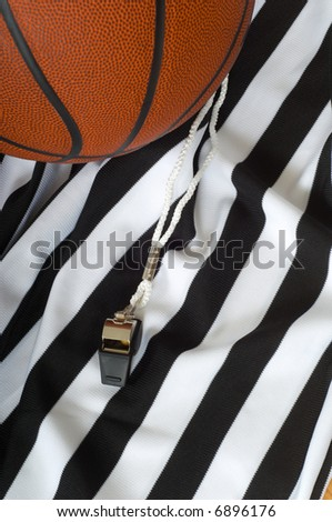 A referee jersy with a whistle and a basketball, basketball referee's equipment - stock photo