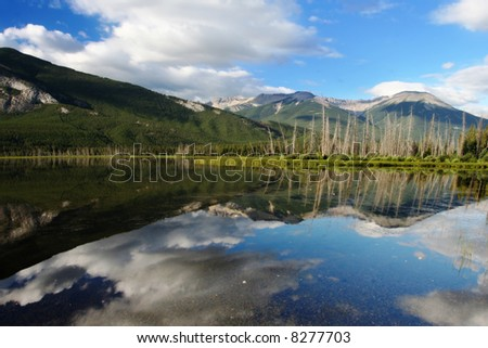 A reflection of a small mountain in the water of a lake located in Banff National Park in Alberta, Canada