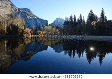 a reflection of half dome of yosemite over merced river