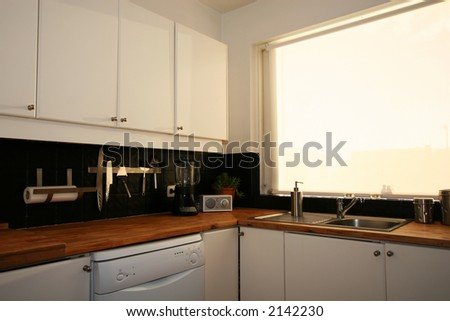 A regular kitchen,, sink, knives, blender, dishwasher and tissue paper visible