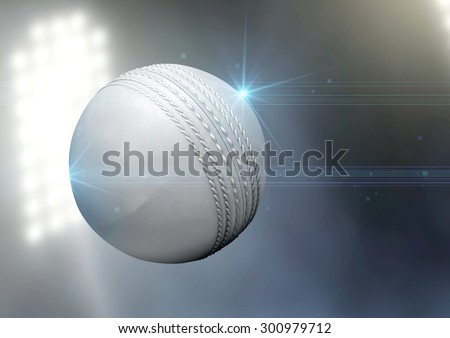 A regular white cricket ball flying through the air on an a outdoor stadium background during the night - stock photo