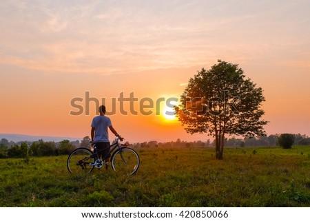 a relaxing farmer on sunset over farmland - stock photo