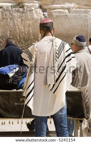 A religious orthodox Jew wearing a prayer shawl draped prays at the Western wall. Jerusalem, Israel. - stock photo