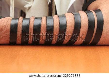 A religious orthodox Jew with arm-tefillin on his left hand prays - stock photo