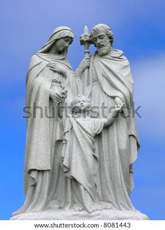 A religious scuplture with a blue sky background.