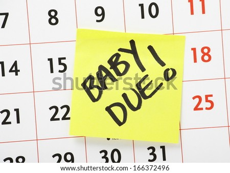 A reminder for when the baby is due written on a yellow paper sticky note and stuck to a wall calendar background - stock photo