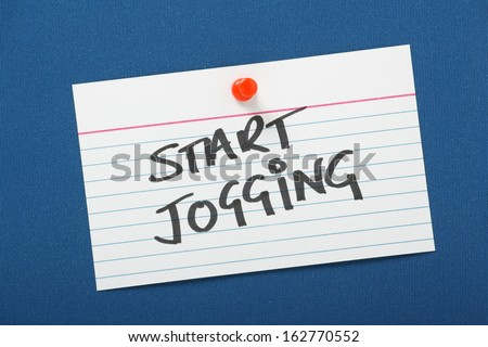 A reminder to Start Jogging written on a white note card pinned to a blue notice board