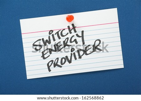 A reminder to Switch Energy Provider written on a note card pinned to a blue notice board. As power and energy providers increase their prices it pays customers to shop around for lower tariffs. - stock photo