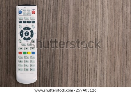 A remote control over a wood background - stock photo