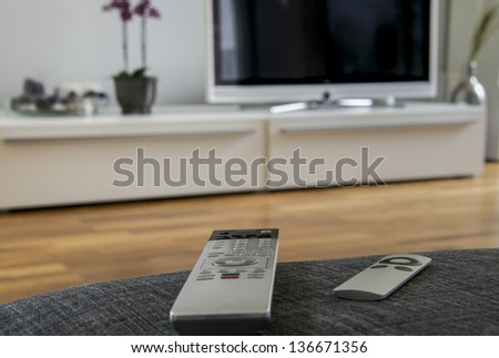 a remote controller is lying on the grey sofa with the home theater in the background - stock photo