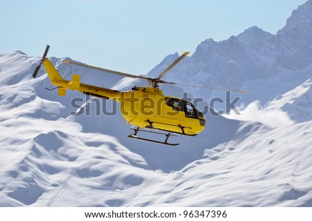 a rescue helicopter in snow covered mountains used to transport injured sports people rapidly from inaccessible mountainous terrain to medical facilities, saving many lives
