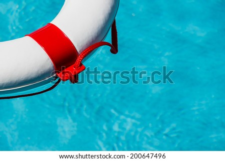 a rescue tire floating in a swimming pool. symbolic photo for rescue and crisis management in the financial crisis and banking crisis. - stock photo