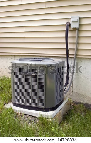 A residential central air conditioning unit sitting outside a home. - stock photo