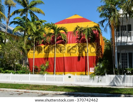 A residential house covered with a red and yellow canvas tent while being fumigated for termites. - stock photo