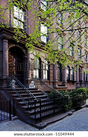 A residential New York, Philadelphia, Boston or Chicago brownstone townhouse building with balck fence and steps in front. - stock photo