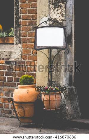 a restaurant. the menu at the entrance to the cafe on the iron leg with space for text. restaurant menu concept for your text. background, vintage old style. old city. poster - stock photo