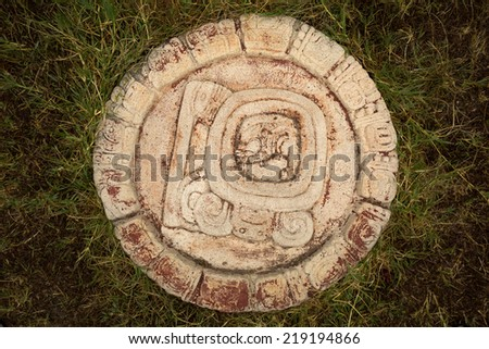 a restored round  Mayan calendar sitting in the grass in Tonina,Chiapas,Mexico - stock photo