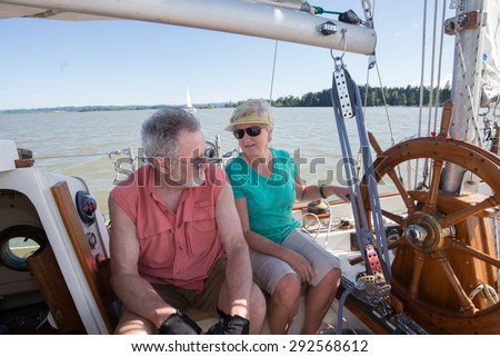 A retired couple on their sailboat converse as they sail on an Oregon lake. - stock photo