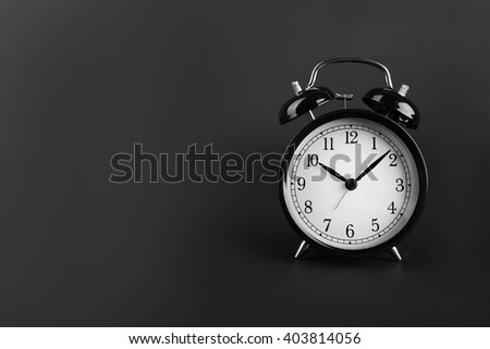 A retro alarm-clock on dark grey background.